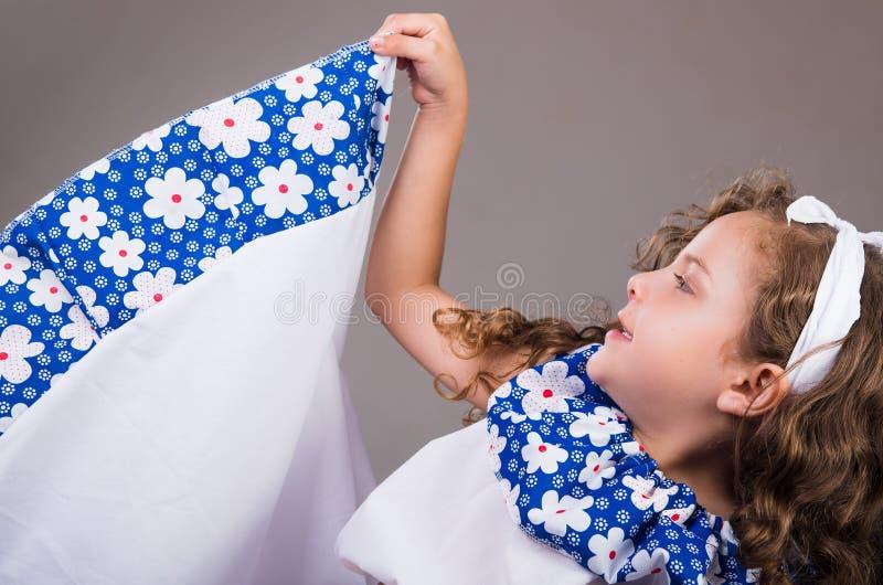 Leuk meisje die mooie witte en blauwe kleding met de aanpassing van hoofdband dragen die, actief voor camera, studio stellen royalty-vrije stock foto