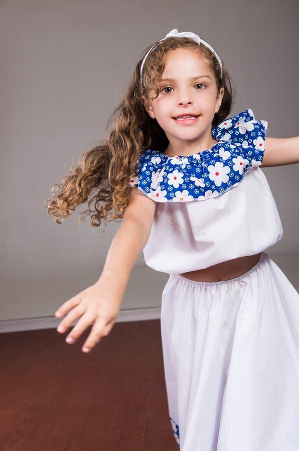 Leuk meisje die mooie witte en blauwe kleding met de aanpassing van hoofdband dragen die, actief voor camera, studio stellen royalty-vrije stock afbeeldingen