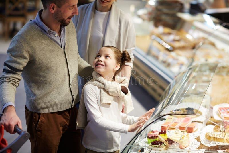 Leuk Meisje die om Snoepjes in Kruidenierswinkelopslag vragen stock foto's