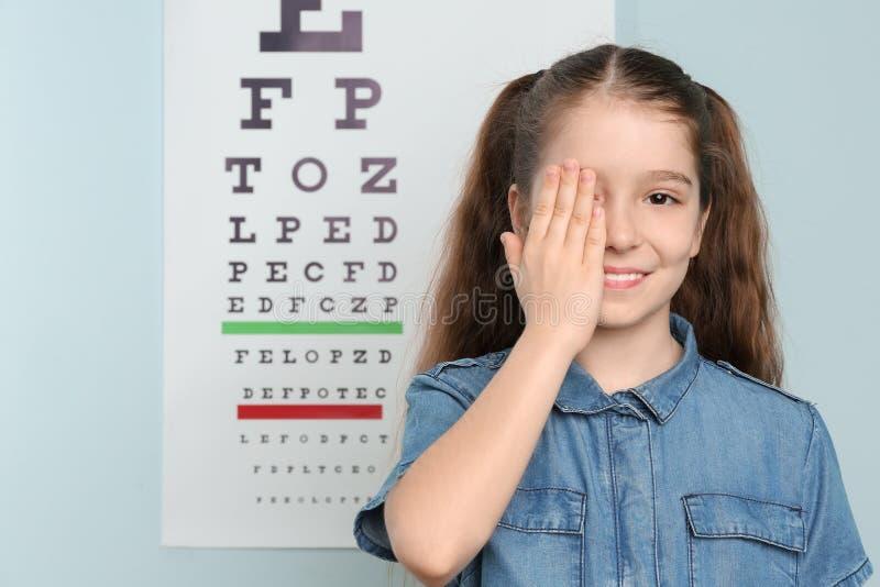Leuk meisje die oog in bureau behandelen royalty-vrije stock afbeeldingen