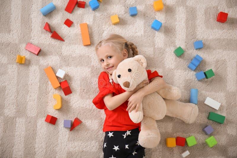 Leuk meisje die op comfortabel tapijt met kubussen liggen stock fotografie