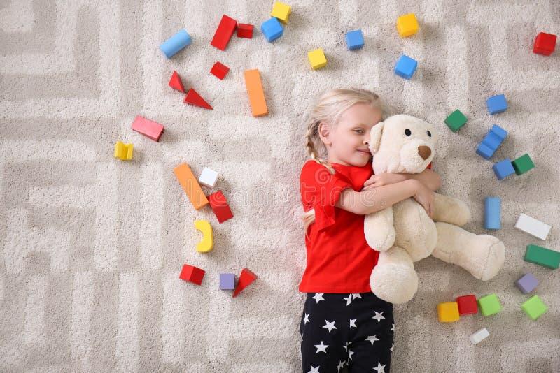 Leuk meisje die op comfortabel tapijt met kubussen liggen stock foto