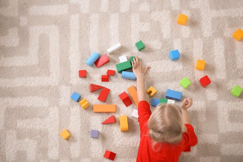 Leuk meisje die op comfortabel tapijt met kubussen liggen royalty-vrije stock afbeelding