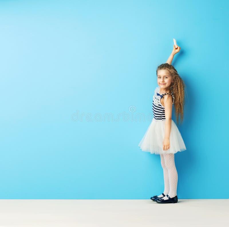 Leuk meisje die op de muur met krijt schrijven royalty-vrije stock afbeelding