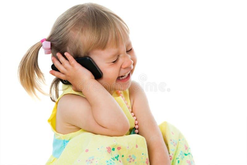 Leuk meisje die op telefoon lachen. royalty-vrije stock afbeeldingen