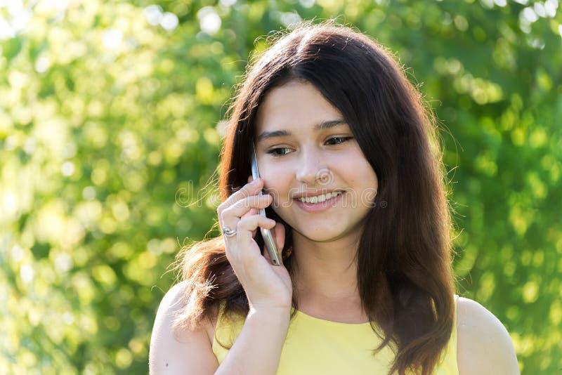 Leuk meisje die op telefoon in park spreken stock fotografie