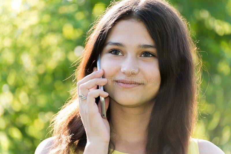 Leuk meisje die op telefoon in park spreken royalty-vrije stock fotografie