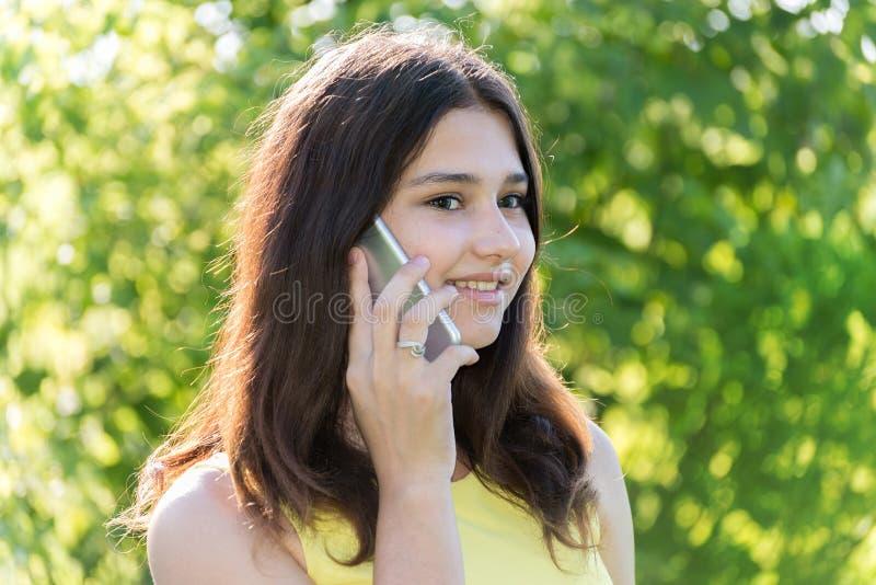 Leuk meisje die op telefoon in park spreken royalty-vrije stock afbeelding