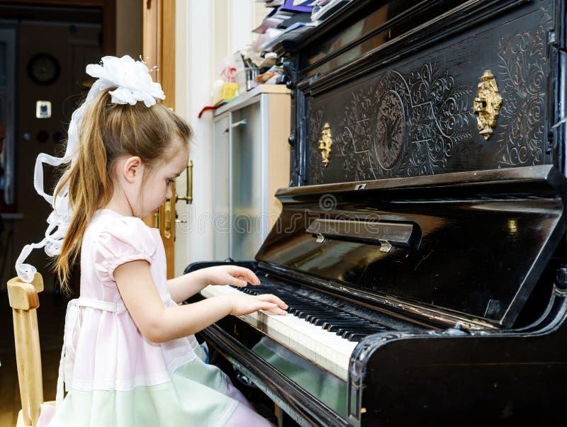 Leuk meisje die oude piano spelen royalty-vrije stock afbeeldingen