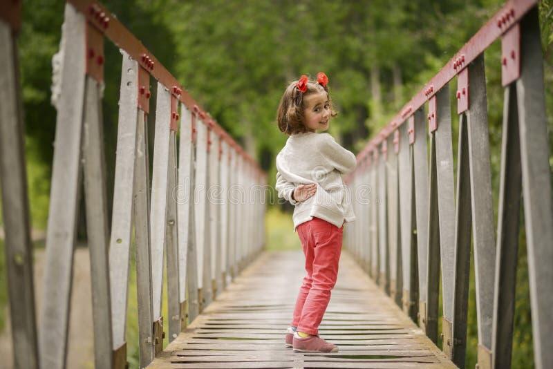 Leuk meisje die pret in een landelijke brug hebben stock foto