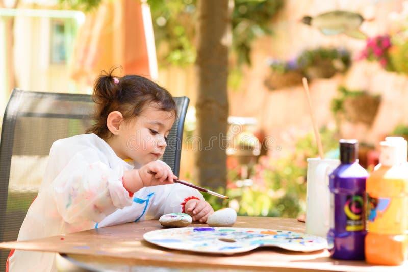 Leuk meisje die pret hebben, met borstel kleuren, en bij de zomer of de herfsttuin schrijven schilderen royalty-vrije stock foto