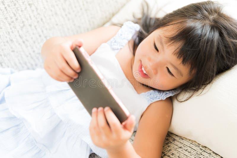 Leuk meisje die pret hebben om spel op slimme telefoon te spelen royalty-vrije stock afbeeldingen