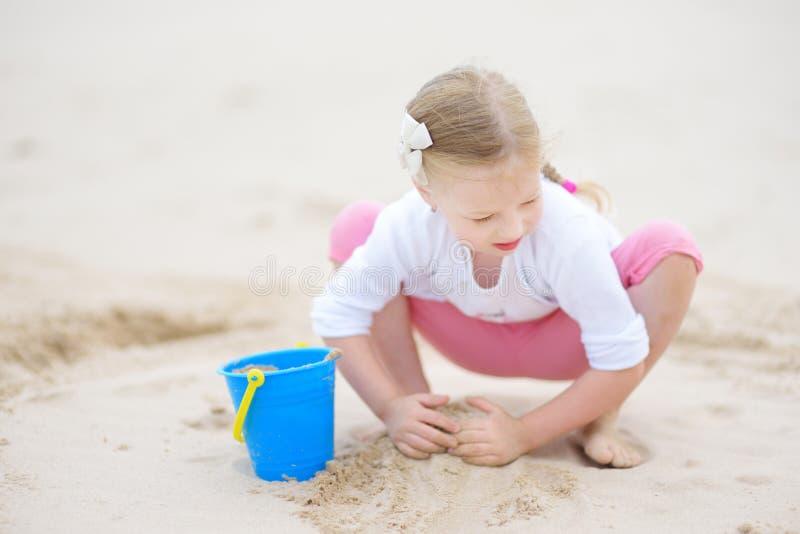 Leuk meisje die pret op een zandig strand op warme en zonnige de zomerdag hebben Jong geitje het spelen door de oceaan stock foto