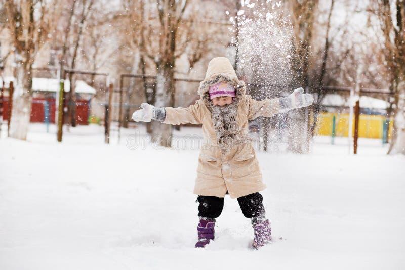 Leuk meisje die in sneeuwpark lopen, gelukkige kinderjaren stock foto's