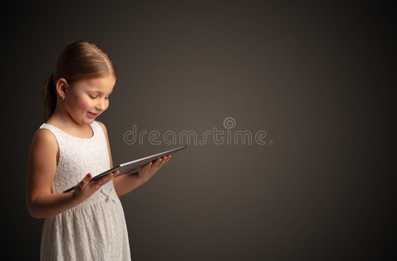 Leuk meisje die tablet met donkere achtergrond gebruiken royalty-vrije stock afbeeldingen