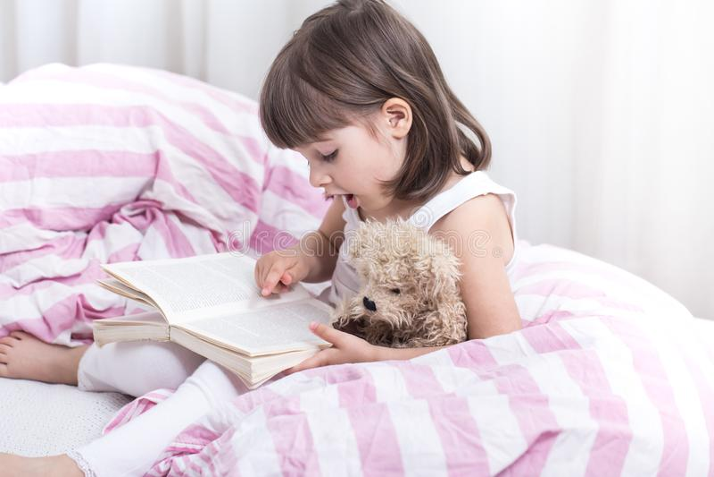 Leuk meisje die terwijl het liggen in een comfortabel wit bed glimlachen royalty-vrije stock afbeelding