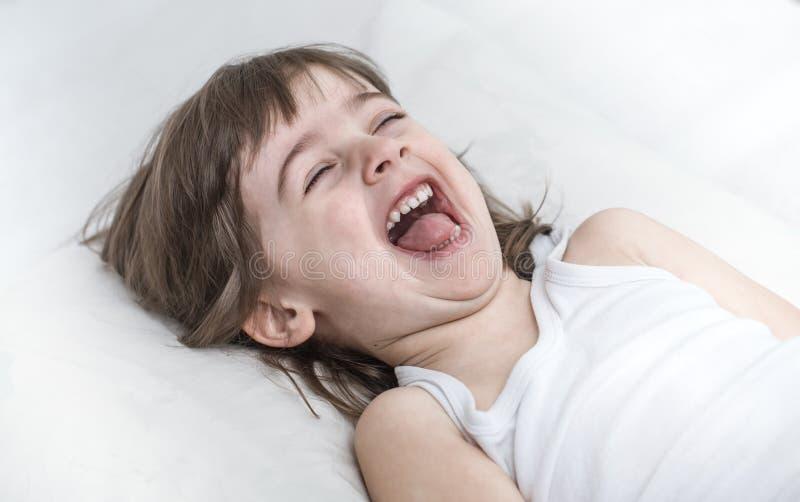 Leuk meisje die terwijl het liggen in een comfortabel wit bed glimlachen royalty-vrije stock fotografie