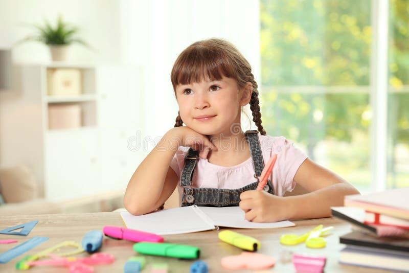 Leuk meisje die thuiswerk doen bij lijst met schoolkantoorbehoeften royalty-vrije stock afbeeldingen