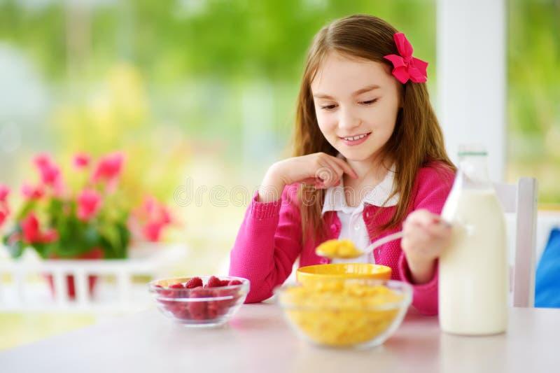 Leuk meisje die van haar ontbijt thuis genieten Mooi kind cornflakes en frambozen eten en consumptiemelk die voor school royalty-vrije stock foto