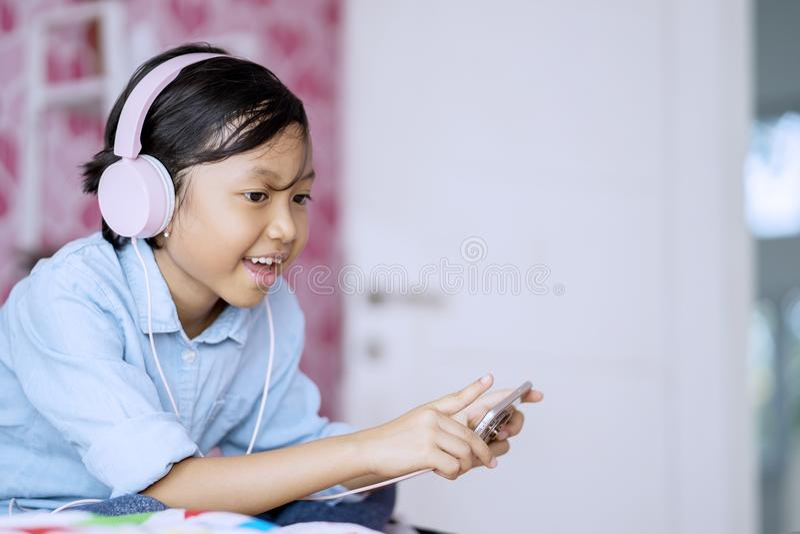 Leuk meisje die van muziek in de slaapkamer genieten stock afbeelding