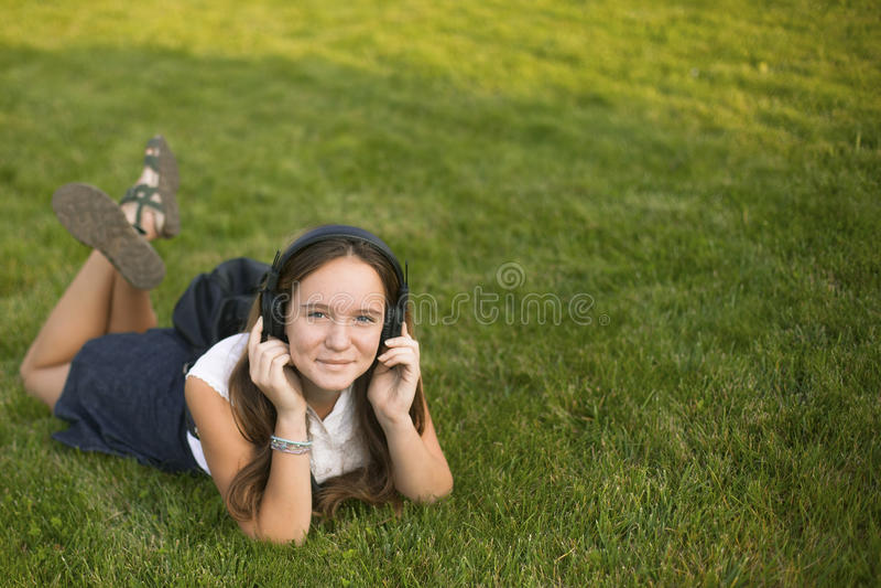 Leuk meisje die van muziek met hoofdtelefoons genieten terwijl het liggen in het gras Met ruimte voor tekst stock afbeeldingen