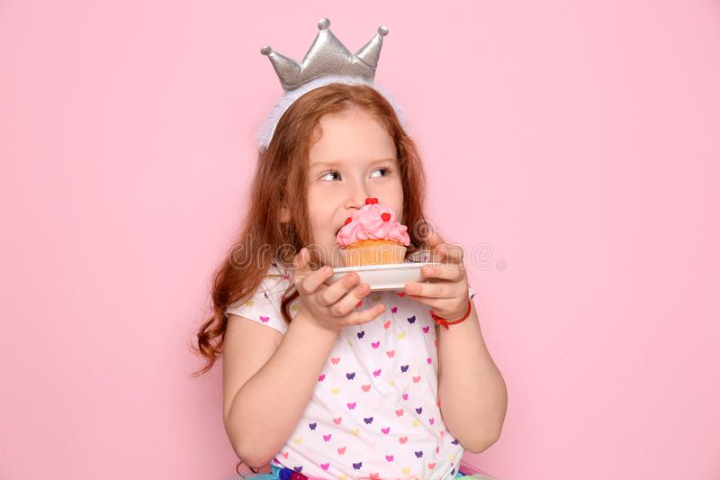 Leuk meisje die verjaardag cupcake op kleurenachtergrond eten stock afbeelding