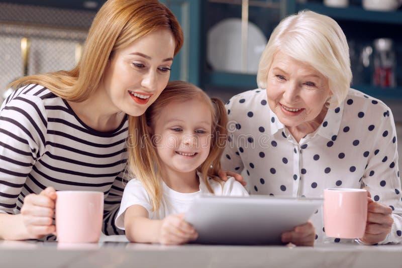 Leuk meisje die video op tablet tonen aan moeder en grootmoeder royalty-vrije stock afbeeldingen