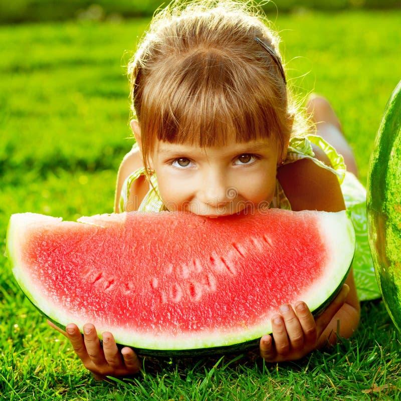 Leuk meisje die watermeloen eten en op het groene gras liggen royalty-vrije stock afbeeldingen
