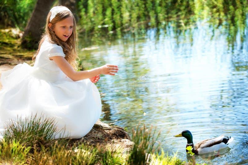 Leuk meisje die in witte kleding een eend voeden. stock afbeeldingen