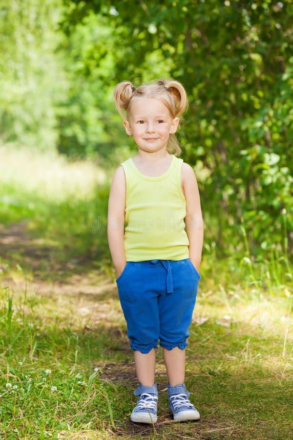 Leuk meisje die zich op een weg in groen park bevinden royalty-vrije stock fotografie