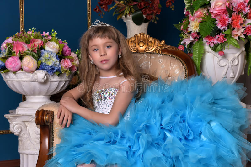 Leuk meisje in een blauwe kledingszitting onder vazen met bloemen stock foto