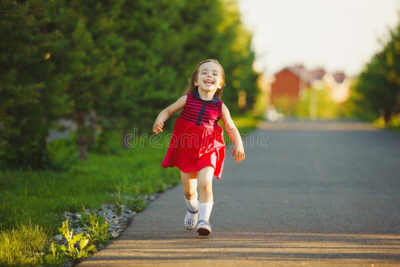 Leuk meisje in een de zomerkleding die langs de steeg lopen royalty-vrije stock foto's