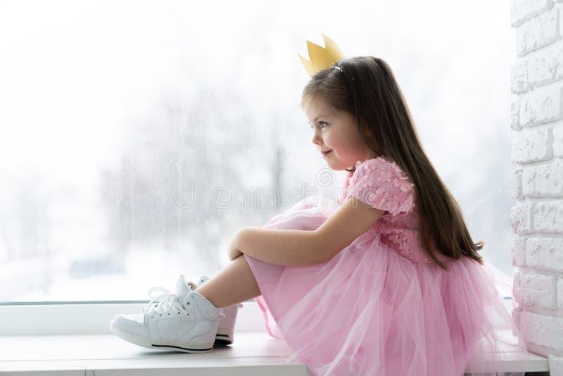 Leuk meisje in een prinseskostuum Mooi kind die voor een kostuumpartij voorbereidingen treffen Mooie koningin in gouden kroon stock afbeelding
