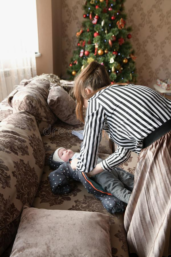 Leuk meisje in een roze kleding die een grote doos met giften houden die dichtbij verfraaide Kerstboom zitten gerlyand stock afbeelding