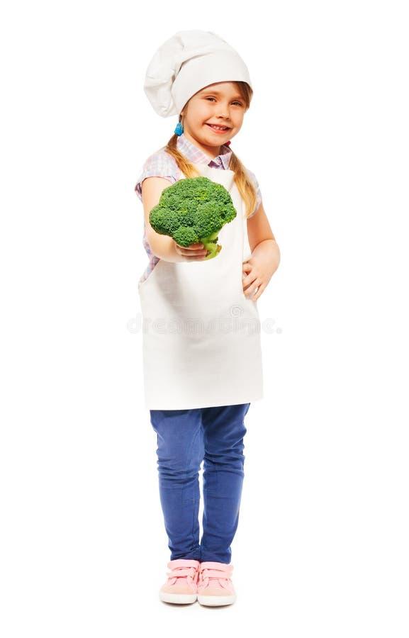 Leuk meisje in eenvormige de holdings verse broccoli van de kok stock afbeeldingen