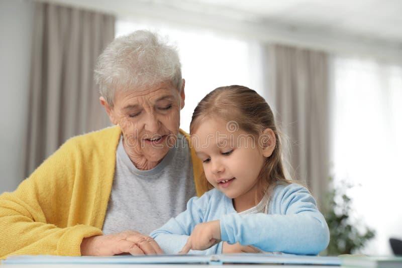 Leuk meisje en haar boek van de grootmoederlezing stock foto