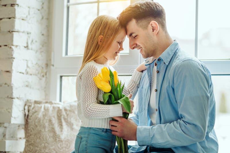 Leuk meisje en haar knappe vader De vader geeft boeket bloeit zijn kleine dochter royalty-vrije stock foto's