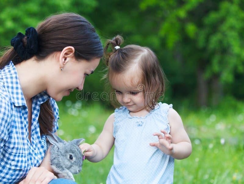 Leuk meisje en haar moeder die weinig grijs konijn koesteren stock foto