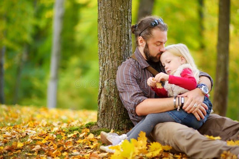Leuk meisje en haar vader die pret op mooie de herfstdag hebben Het gelukkige kind spelen in de herfstpark Jong geitje die gele d royalty-vrije stock afbeeldingen