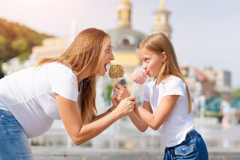 Leuk meisje en haar zwangere moeder die suikergoedappelen eten bij markt in pretpark Gelukkige houdende van familie Moeder en stock afbeeldingen