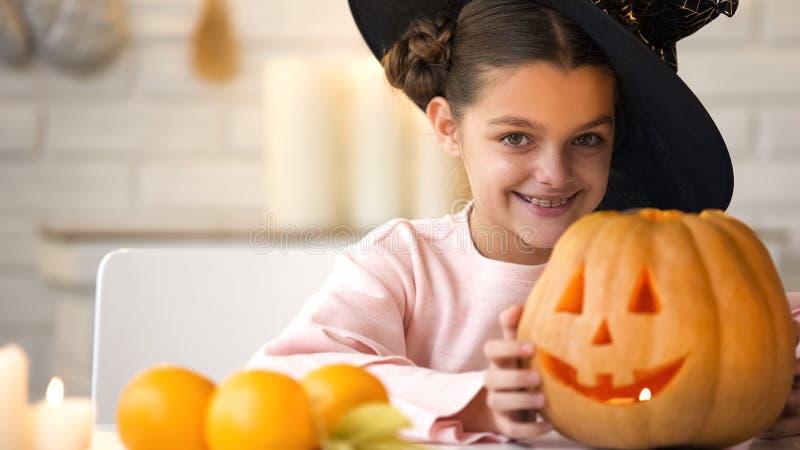 Leuk meisje in heksenkostuum die hefboom pompoen en glimlachen tonen, die voor partij voorbereidingen treffen stock fotografie