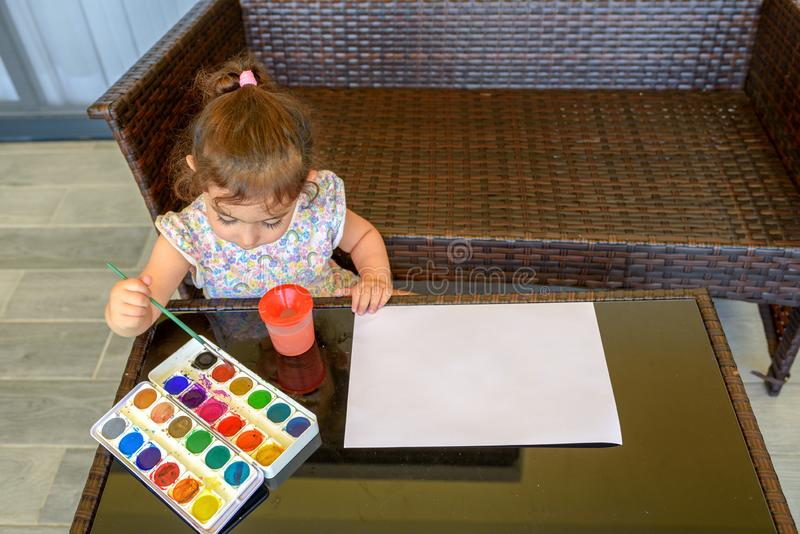 Leuk meisje het schilderen beeld op huis binnenlandse achtergrond Jongen en de meisjes die bij het surfen van bureau de zitten en royalty-vrije stock afbeelding