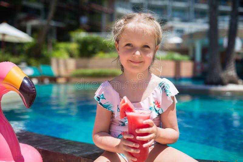 Leuk meisje in het zwembad van de zwempakzitting dichtbij met opblaasbare roze flamingo en het drinken vers watermeloensap De zom royalty-vrije stock afbeeldingen