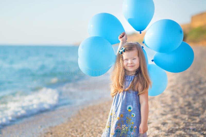 Leuk meisje met ballons die op strand van oceaan overzeese kust met zandig rotsachtig land, een vakantie, een overzeese reis stel royalty-vrije stock foto's