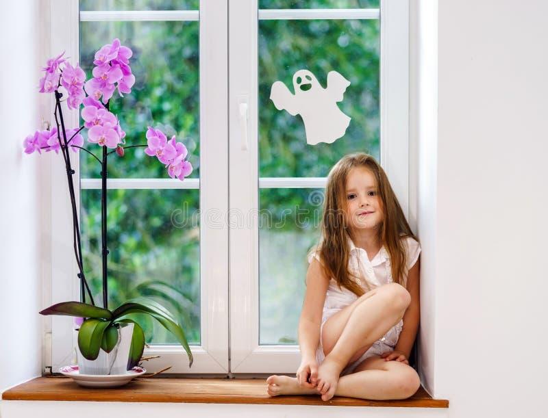 Leuk meisje met bloemzitting op vensterbank van nieuwe pvc-wi stock foto's