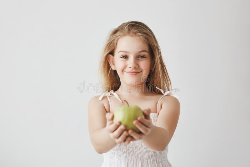 Leuk meisje met blond lang haar en blauwe ogen in witte kleding die, appel in handen houden brightfully glimlachen die en stock foto's