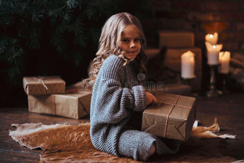 Leuk meisje met blonde krullend haar die een warme sweater dragen die een giftdoos houden terwijl het zitten op een vloer naast stock afbeelding