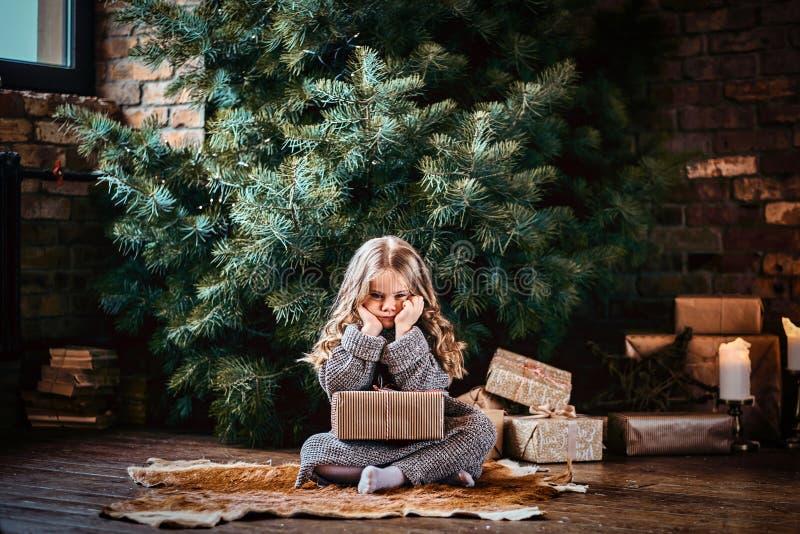 Leuk meisje met blonde krullend haar die een warme sweater dragen die een giftdoos houden terwijl het zitten op een vloer naast royalty-vrije stock afbeeldingen