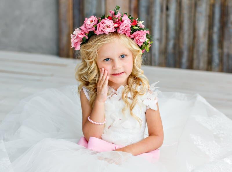 Leuk meisje met blondehaar in een heldere studio met een kroon van roze bloemen Het bekijken de camera en het glimlachen royalty-vrije stock fotografie