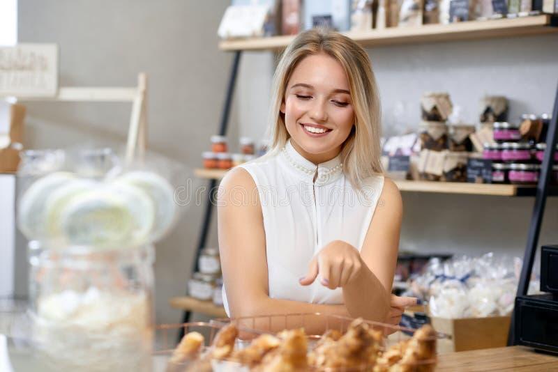 Leuk meisje met blondehaar het kopen croissants in lokale winkel royalty-vrije stock afbeeldingen